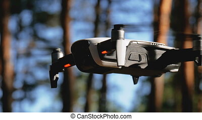 Drone with a camera hovers in the air. Quadcopter flies...