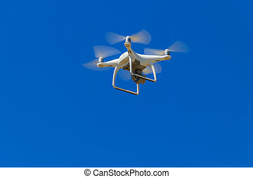 Drone with camera flying in blue sky