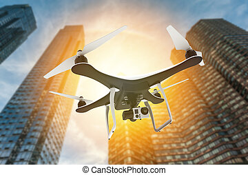 Drone with digital camera flying in front of skyscrapers at sunset