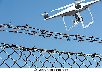 Drone with digital camera flying over a barbed wire fence