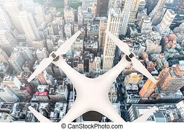 Drone with digital camera flying over a big city in sunlight