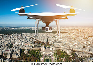 Drone with digital camera flying over a big city