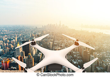 Drone with digital camera flying over a modern city at sunset