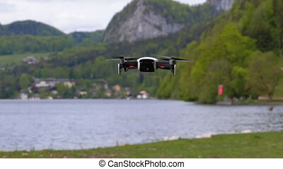 Drone with Rotating Propellers Hanging in the Air on a...