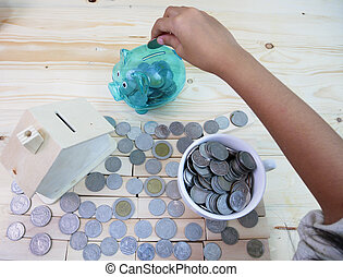 Drop coins in a piggy bank around a house and a glass of coins