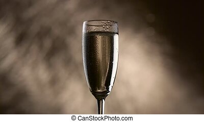 Drop drips down the wall of a glass with champagne on a bokeh background