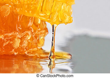 drop of honey dripping from the honeycomb closeup