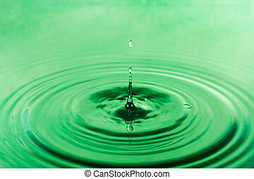 Drop of water falling into the green water