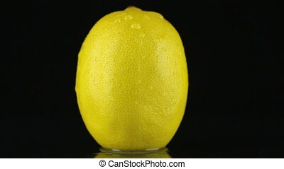Drop of water flows down the skin of an lemon