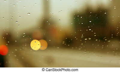 Drop on a glass window and a blurred landscape on the background