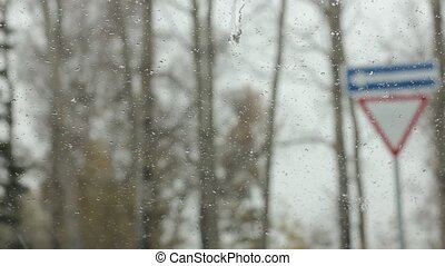 droplets on a windshield on the day snow with rain. blured...