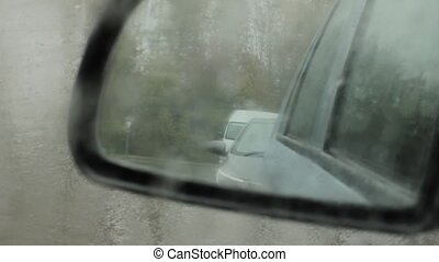 droplets on side mirror, blurred car in side mirror view on...