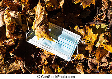 dropped sanitary mask in fallen leaves close up