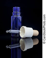 Dropper bottle with pipette on black background