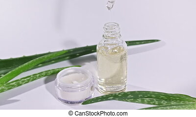 Dropper glass bottle with Aloe Vera oil. Cosmetics based on Aloe Vera extract. White facial cream jar. Skin and body care on white background. High quality 4k footage