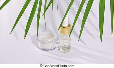 Dropper glass bottle with natural cosmetic, essential oil. White facial cream jar. Skin and body care. Motion of tropical palm leaves with shadows on white background. High quality 4k footage