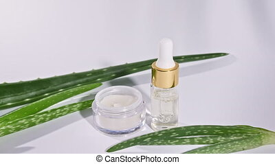 Dropper glass bottle with natural cosmetic, oil Aloe Vera. White facial cream jar. Skin and body care. Motion of tropical palm leaves with shadows on white background. High quality 4k footage