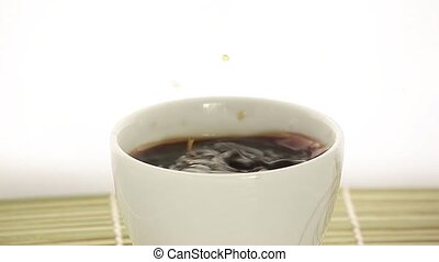 dropping coffee - coffee drops into a white cup with white...