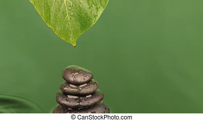 Dropping drops of water from a green leaf on a pyramid made...