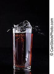 Dropping ice into a glass with a cold drink. Splash of drink in the bar.