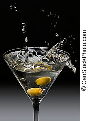 Dropping two olives into a martini glass