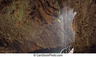 Drops drip into the water in a small cave . Waterfall in...