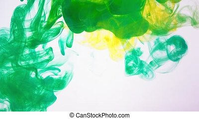 Drops of color ink swirling in a water isolated on white background. Abstract background of acrylic ink in water. The paint dissolves into water