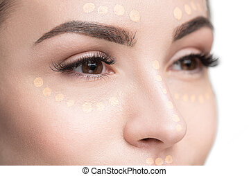 Drops of concealer on female visage - Attractive young lady...