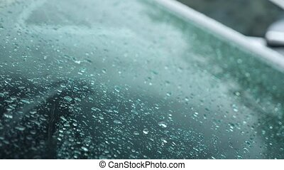 Drops of rain fall on the glass of the car parked outside....