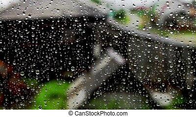 Drops of rain on a window on a nature background