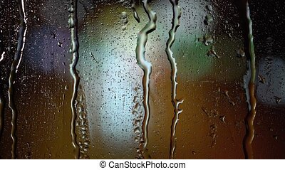 Drops of rain on the glass at night . Blurry background -...