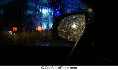 drops of rain on the side window of the car. night in the city