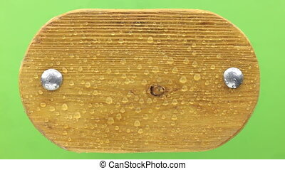 Drops of water fall on a wooden board with iron rivets. Isolated on green background.