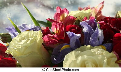 Drops of water falling on beautiful bouquet of roses, iris and alstroemeria.