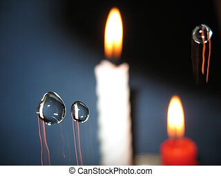 Drops of water on a background of burning candles