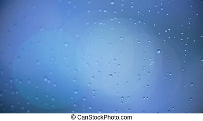 Drops of water on the evening window - night lights through...