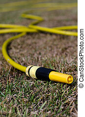 Drought - Close up of a yellow gardening water pipe lying ...