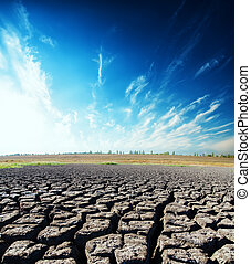 drought earth closeup and deep blue sky with clouds in sunset time