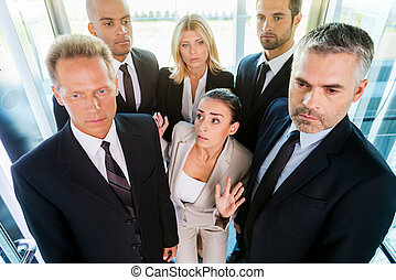 Drowning in people. Top view of fearful young woman in formalwear feeling trapped by the crowd while standing in elevator