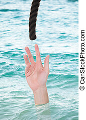 Drowning Man Reaching For Rope - Man reaching for rope while...