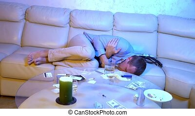 Drug abuse: A young man in an office shirt sitting at a desk, drugs and pills in front of him. beats in convulsions. overdose.