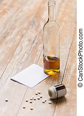 bottle of alcohol and pills on table