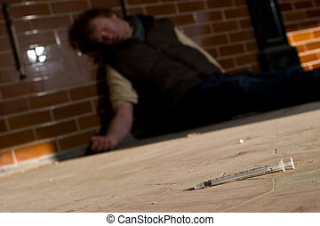 Drug abuse - drug using man passed out on the floor with ...