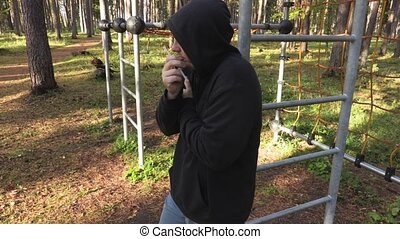 Drug addict in a park with a syringe