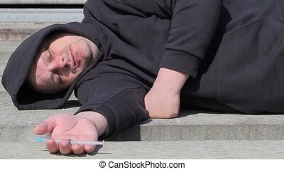 Drug addict man sleeping with syrin