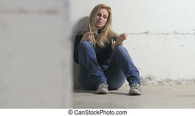 young blonde girl injecting heroin cocain crack sitting on the ground of dirty dark underground parking dolly shot