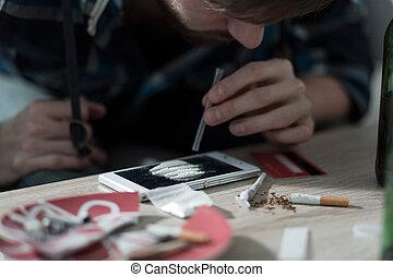 Drug addicted man taking cocaine - Close-up of drug addicted...
