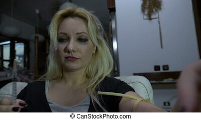 Drug addicted single mother preparing her shot of heroin and...