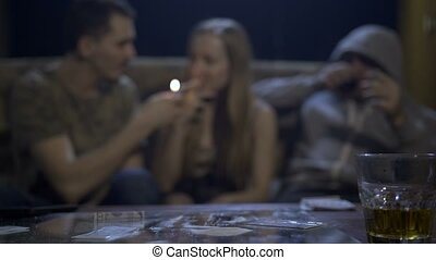 Drug addicted youth using cocaine at the table in a gloomy...