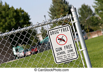 drug and gun free school zone sign at a school yard. sign of...